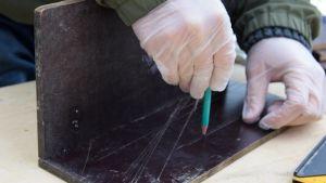 Två skivor i vattenfast faner som spikats ihop till en vinkel. En hand ritar ut markeringar på skivan med en blyertspenna.
