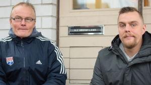 Två män sitter på huk nära ett brevinkast.