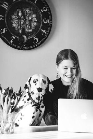 Blond kvinna ler och ser ner mot en dator. Bredvid henne sitter en dalmatin.