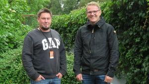 Två män i en lummig trädgård. Svagt regn. De ser glada ut.