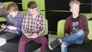 Tre unga män sitter på soffa med blicken vänd bort från varandra. Det gemensamma låtskrivandet har sinat ut.