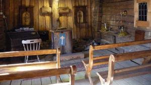 ett litet kapell  inrymt i en byggnad som fungerat som ladugård. Träbankar, och kors på väggen  gjort av gamla stockar.