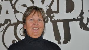 Närbild på en leende Ulla Nummelin som står framför en vägg med bilskolans logotyp i bakgrunden.