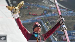 Dawid Kubacki lyfter upp pokal och skidor mot skyn.