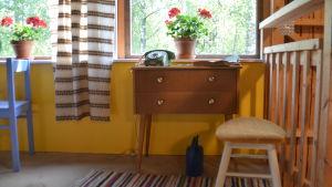 Ett telefonbord med gammalt bordstelefon och telefonkatalog. Pelargon i fönstret.