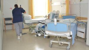 En städare torkar golv i ett rum på en bäddavdelning.