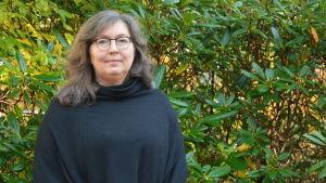En kvinna framför en rhododhendronbuske.