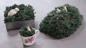 Tre olika påskgräs gjorda av garn på ett bord
