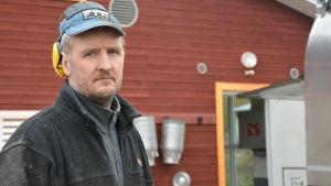 En man med hörlurar och klädd i arbetskläder utanför en ny ladugård.