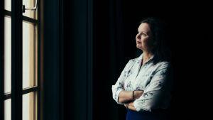 På bilden ses författaren Ann-Luise Bertell titta ut genom ett fönster iklädd en ljus skjorta och blå kjol mot en mörk bakgrund.