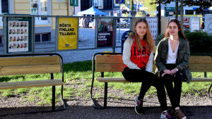 Gymnasieeleverna Amanda Salin och Anna Ring poserar framför några valaffischer inför EU-valet vid Ekenäs torg.