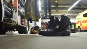 Skor på golvet i en brandstation, färdiga att ta på sig vid utryckning.