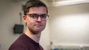 Manlig teknologstuderande med glasögon och röd tröja