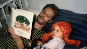 En liten flicka med pippi långstrump-peruk ligger i sängen. Hennes pappa läser en saga till henne.