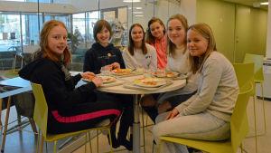 Flickor som sitter och äter i en skolmatsal.