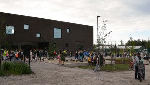 Skolbyggnaden och många männiksor ute på gården.
