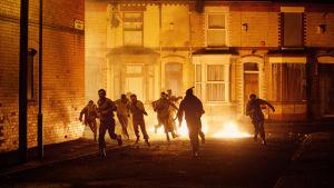Juoksijoita öisellä kadulla. Kuva elokuvasta '71.