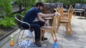 En ung man sitter utomhus på en bakgård och putsar sotiga stolar som har smutsats ner på grund av brand inne i ett restaurangkök.