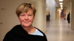 Rektorn för Hangö högstadium står i en tom skolkorridor och ser mot kameran.