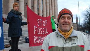 """Klimatdemonstrant på riksdagens trappa, med röd banderoll med texten """"Stop fossil burning""""."""