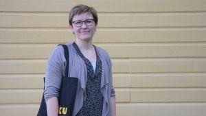 En kvinna med glasögon står framför en gul vägg, hon har en tygkass med gul text på, det står Riku på den.