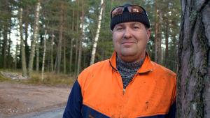 Kim Hasselberg står i orange arbetskläder vid en väg.