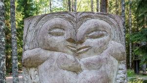 En stenstaty som föreställer två ansikten.