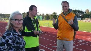 Mirja Koponen och hennes man Arto samt idrottsinstruktör Heikki Kiili på Karis idrottsplan en solig kseptemberkväll. Heikki visar tummen upp.