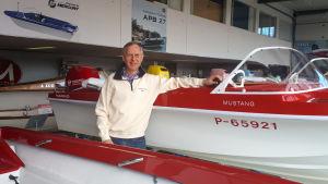 En man står och håller armen om en kanten på en röd motorbåt i en utställningshall.