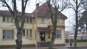 Ett gult trähus inne i en stad. Det är Karis ungdomsgård, Villa Haga en mulen, snöfri januaridag 2020