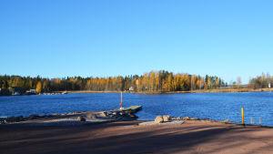 Vy från strand. Man ser en brygga vid vilken en motorbåt är fäst samt en ö mittemot.