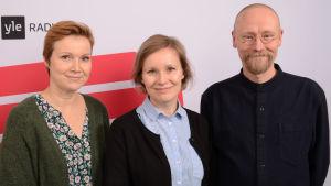 Sari Valto, Monika Luukkonen och Sangen Salo fotograferade vid en affisch där det står Yle.