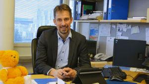 Sektorchef vid HUCS Jari Petäjä sitter bakom sitt skrivbord i kontoret i Barnets borg.