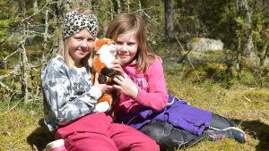 Hanna och Tyra sitter i gräset med skogen som bakgrund. De håller i ett mjukisdjur som föreställer en räv.