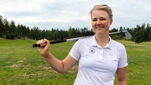 En ung kvinna står på en gräsmatta och håller en golfklubba över axeln.