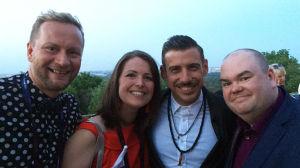 Tre män och en kvinna poserar på en takterrass