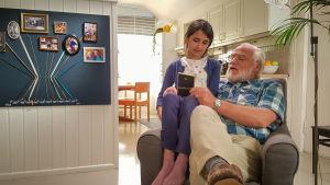 Cilla sitter i en portfölj med sin morfar och tittar på ett fotografi.