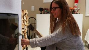 En kvinna håller på att sätta in ved i en kakelugn.