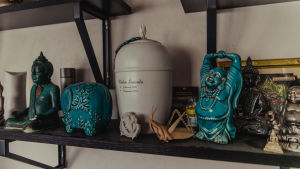 En urna på en hylla med olika buddhastatyer.