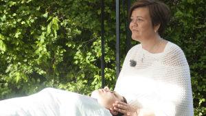 Tiina rentoutuu refleksologi Tarja Hirven käsittelyssä