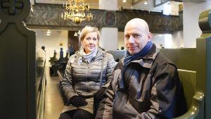 En kvinna och en man sitter i kyrkbänken inuti Borgå domkyrka.