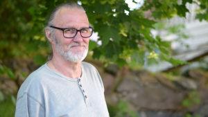 Frank Holmlund i grå tröja står vid ett träd.