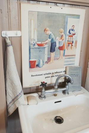 Vanha pesuallas, jonka yllä juliste, jossa neuvotaan asianmukaista käsienpesua ennen ruokailua.
