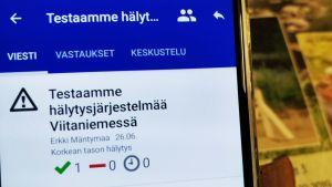 Älypuhelimen näytöllä tieto Secapp-hälytysjärjestelmän testaamisesta Gradian tiloissa Jyväskylän Viitaniemessä.