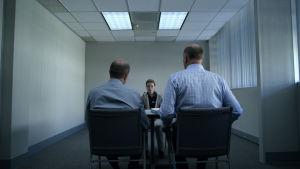 En flicka sitter i ett polisförhör med ansiktet riktat mot kameran. På bilden syns två manliga poliser sitta vid förhörsbordet med ryggen mot kameran.