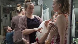 Emppu provar den klänning hon skall använda då hon våldtas på scenen.