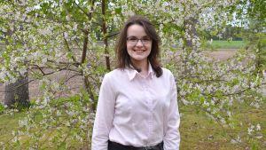 Linnéa står vid blommande äppelträd.