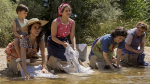 Dne unga Salvador med sin mamma och en hop andra kvinnor under tvättdagen vid ett vattendrag.