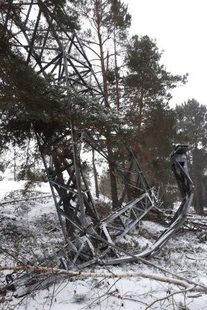 Förvriden metall ligger på en snöig mark efter att masten till en högspänningsledning gått av i en vinterstorm.