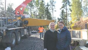 Två kvinnor tittar in i kameran och ler. Bakom dem finns skog och byggmaskiner.